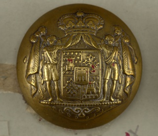 "Circular convex button with ornament showing coat of arms on shield two angel supporters and mantling of drapery held by a crown. Brass back and shank. On reverse, ""Superieur France.""