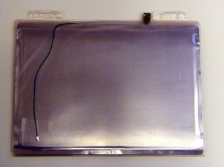 """Rectangular silver and blue-green padded vinyl case (-1a) with shoulder strap on one side, flap at opposite side.  Flap unsnaps allowing case to open in notebook-like fashion, revealing bracket along inner spine.  Bracket can be opened to accept flat rectangular """"packets"""" (-1c/j) inserted in any quantity or combination, as pages in a book.  Rectangular translucent orange vinyl case (-1b) with metal strip of electronic ports along exterior spine, flap opposite.  Flap unsnaps allowing case to open in notebook-like fashion (-1b cannot hold """"packets"""").  There are eight """"packets,"""" including: screen (-1c), keyboard (-1d), motherboard (-1e), drive (-1f), battery (-1g), and three blanks (-1h/j)."""