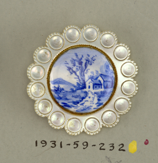 Flat button of pearl shell with scalloped edge and center showing landscape; brass shank.  On card 32