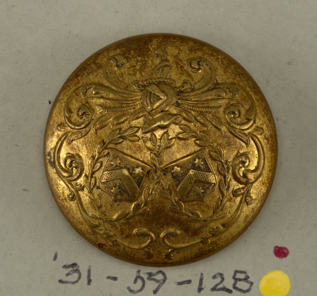 """Circular, convex button with ornament showing two shields with heraldic devices placed within wreaths; leaf mantling with helmet topped by clown's head. Brass back and shank. On reverse, """"Perfectionne E B Paris"""" arranged on a band representing a belt.  On card 45"""