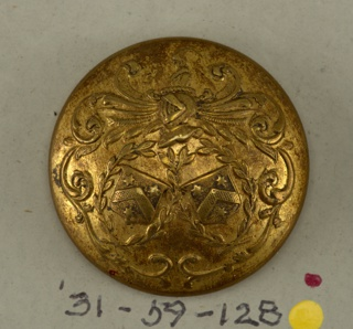 "Circular, convex button with ornament showing two shields with heraldic devices placed within wreaths; leaf mantling with helmet topped by clown's head. Brass back and shank. On reverse, ""Perfectionne E B Paris"" arranged on a band representing a belt.