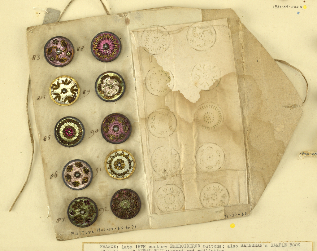 Folding envelope of paper with tie closure; used as a case for ten circular buttons.  On card 14