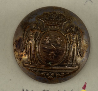 "Circular, convex button with coat of arms showing oval with three fleur-de-lis, angel supporters, and crown. Brass back and shank. On reverse ""Perfectionne El Paris.""