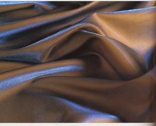 Yardage of full manufactured width, yellowish orange cotton with blue iridescent highlights.