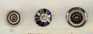 Flat circular button with shanks, varying. -a: engraved pearl and steel beads arranged in rings; -b: flower with petals of colored steel; -c: pearl and colored steel in rings; -d,h: smoked pearl and cut steel; -f,g,j,m: engraved pearl centers on disc of steel; -e,k,l,n: ornamented steel centers on pearl discs; -i: pearl shell, colored yellow, and set in steel rim.   Components -a/-c,-e/-g/-j,-k,-m,-n are on card 31