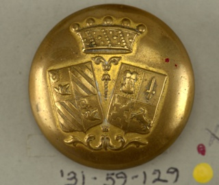 "Circular, convex button with ornament showing two shields with heraldic devices; two leaf motifs and a crown. Brass back and shank. On reverse, ""au pavillion de Rohan Mon. Carriere.""