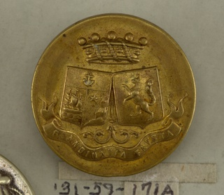 "Flat button showing ornament of two shields with heraldic device, a crown above and below, a ribbon with ""Scandinavia Faustia"". Back of tin with brass shank. On reverse, ""Agry 14 Re Castiglione Mon. Bouvet"".