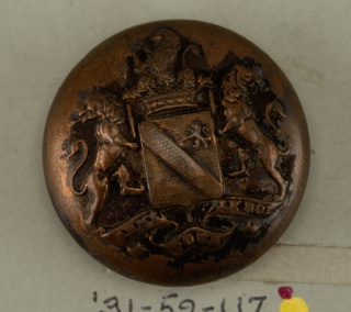 "Convex button ornamented with shield showing heraldic devices held by leopard supporters standing on ribbon with ""Arme pour le Roi""; surmounted by crown and crest. Copper back and shank. On reverse: ""[Bo] uvet 14 Rue Castiglione.""