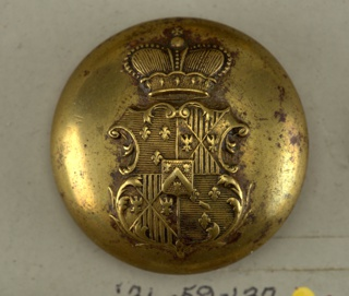 "Circular, convex button; ornamented with cartouche bearing coat of arms, surmounted by a crown. On reverse, ""Agry 14 rue Castiglione Mon. Bovvet."" Brass shank.