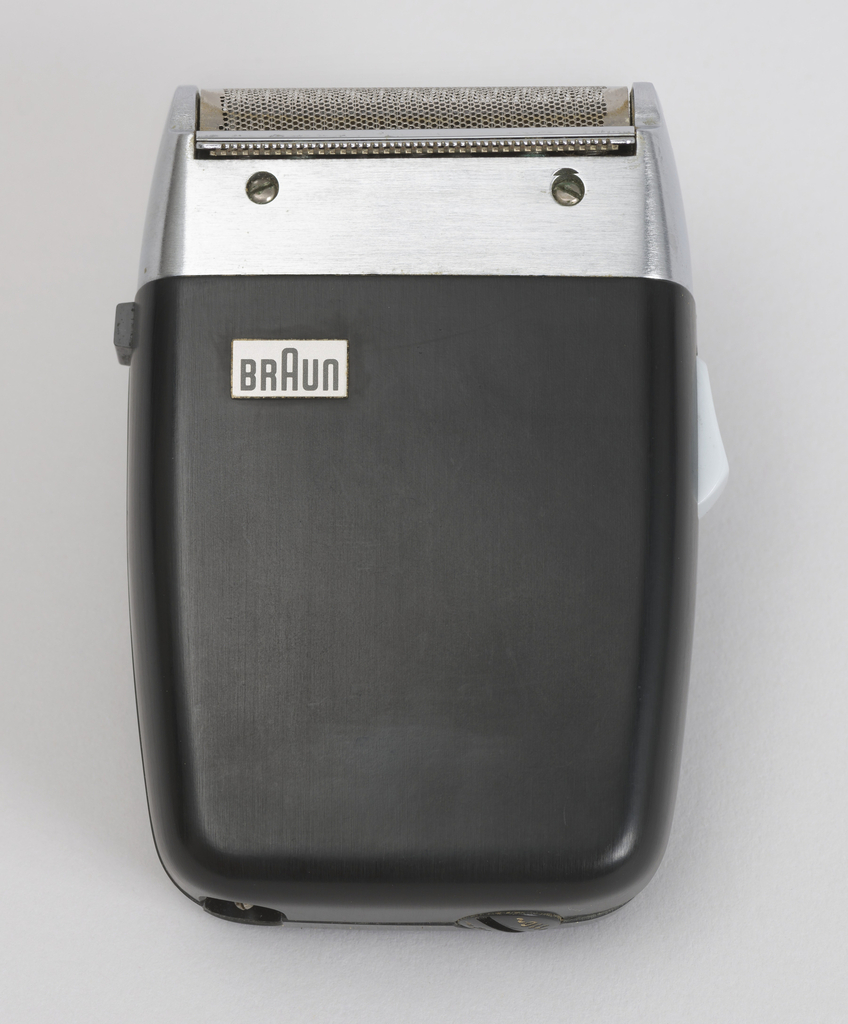 electric shaver with black plastic housing, rounded edges, metal top with razor blade. Light gray switch on one side, black switch on the reverse side. Switch for 110a/220aV