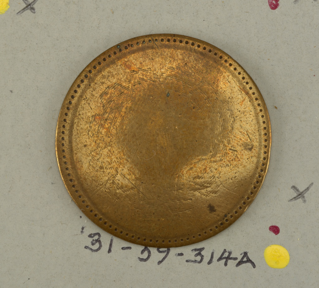 circular nearly flat button with engraving at the edge and an [almost obliterated] ornament in center -  copper shank.  on card 44