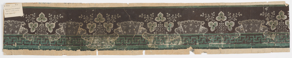 Imitation lace is superimposed at intervals over the fret at the bottom of the design. Above, sections of lace alternate with groups of three three-petaled flowers and foliage. Printed in gray, white, green and black on dark brown ground.