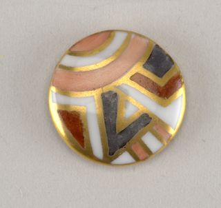Circular molded porcelain button (commercial blank). Slightly domed obverse decorated with abstract geometric motifs in rose, rust, grey, and gold. Reverse with molded shank.