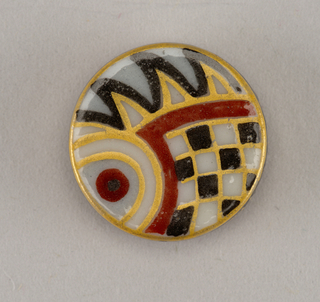 Molded circular porcelain button blank. Flat obverse decorated with sty- lized fish scale and fin motif in red, black, and gold. Reverse with molded rectangular shank, black and gold border.