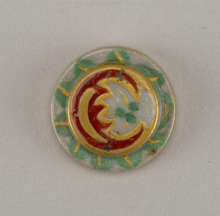 Circular,molded porcelain blank. Obverse with stepped flat center, deco- rated with leaves and stylized flame-like motifs in green and red enamel, with gilded details. Reverse with molded recessed shank, grey border, and gold edges.