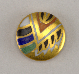 Circular, molded porcelain blank. Slightly domed obverse with geometric and stylized fish motifs in green, blue, black, and coral enamel, with gilded edge. Reverse with molded shank, and with two gold bands.