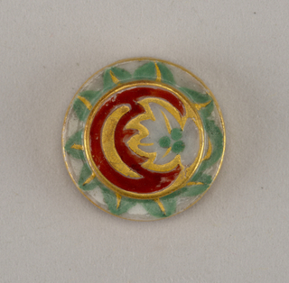 Circular, molded porcelain blank. Obverse with stepped flat center, deco- rated with leaves and stylized flame-like motifs in green and red enamel, with gilded details. Reverse with molded recessed shank, grey border, and gold edges.