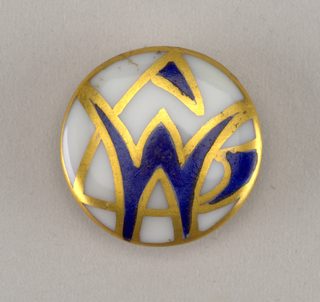 "Circular, molded porcelain blank. Obverse slightly domed, decorated with stylized monogram ""M L"" in blue enamel with gilded edges. Reverse with molded shank, decorated with three gold bands and initials ""S L"" in gold."