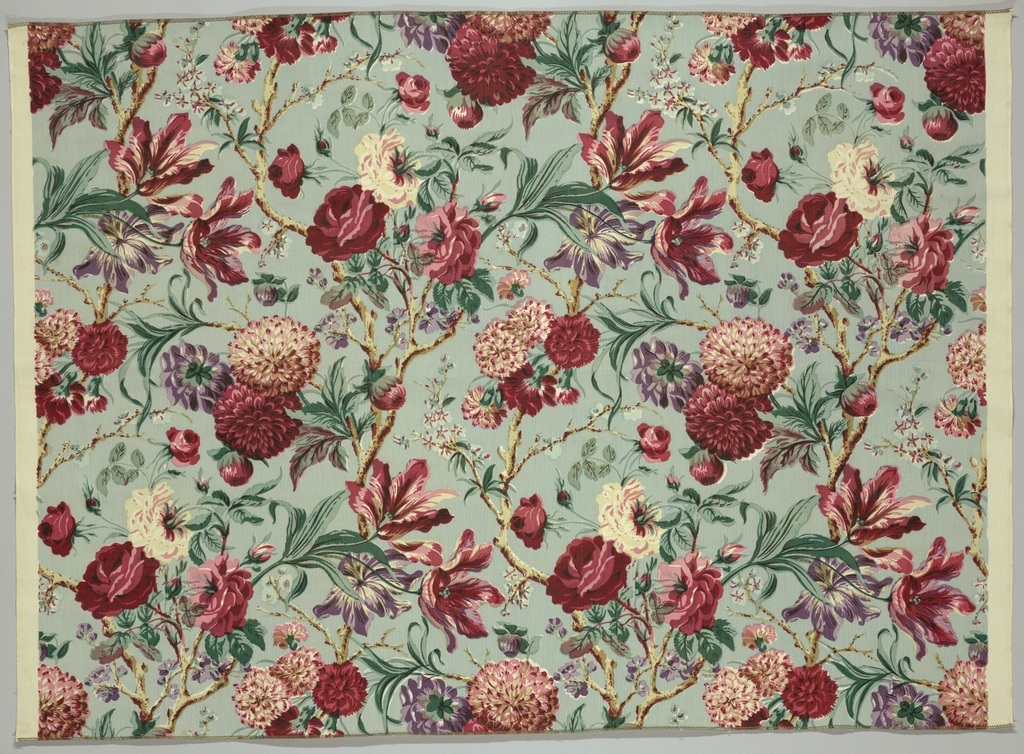 Reproduction-style fabric with a design of oversized flowers, tulips and roses, in shades red, blue and green on a pale blue ground.