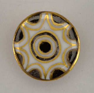 Circular, molded porcelain blank. Obverse flat, decorated with border of black semicircles surrounding central circle edged in gold. Reverse with molded shank, gilded overall.