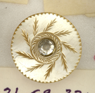 Circular buttons with a central brilliant of white glass set in engraved leaves of seaweed type and milled edge.  On card 29