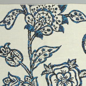 Linen panel screenprinted in shades of blue showing an allover large floral pattern that resembles English crewel work embroidery.