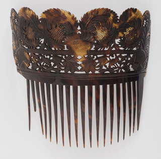 Large tortoiseshell comb with long teeth and carved floral and leaf motifs