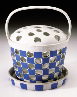 Small circular basket form with strap handle at top, circular lid, and circular dish beneath. Basket and dish with light blue and white checkerboard pattern, the white squares piereced with large circular holes; white lid pierced.