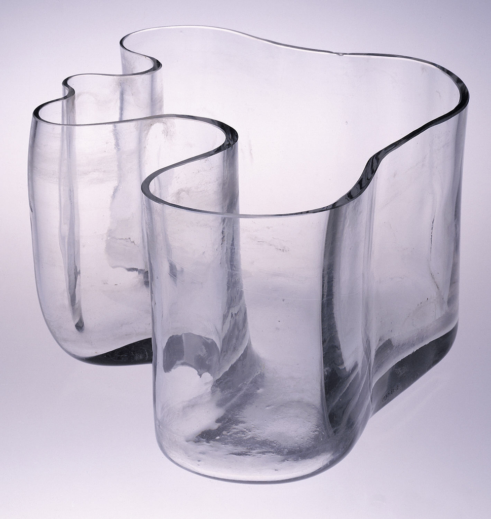 Tall, irregularly-shaped clear glass vase with flat bottom; thickness of wall varies throughout.