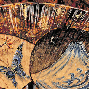 A fan shaped vase sitting on two feet. The vase is a brown and black marbled color with a mountain night scene and a floral (with butterfly) day scene on the front.