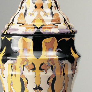 Vase and cover decorated with loose symmetrical abstract pattern in black, orange, yellow, and purple. Shaped cylindrical form undulating into a cone-like lid with pointed knob.