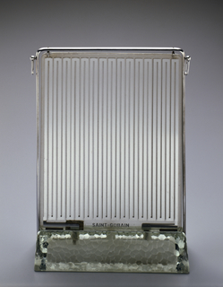 Upright, flat rectangular plate glass sheets with flat metallic heating elements sandwiched between; surrounded by tubular chromed metal frame with rings at upper corners and set into long triangular base of thick tempered glass.