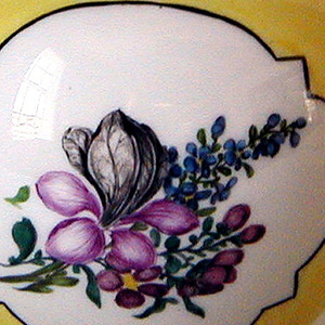 Globular body, scrolled strap handle; spout terminating in a dog's head; cover with flower in high relief, round the base of which is a metal ring.  Body yellow, with two shaped panels outlined in gold and black bands, of white reserve with bouquets of flowers; smaller panels on cover.
