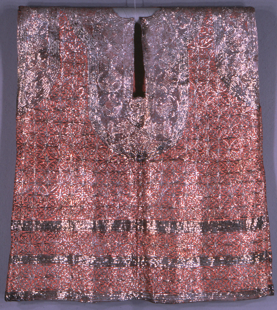Sleeveless tunic of salmon-pink silk embroidered solidly with flat strips of silver foil in a geometric design.