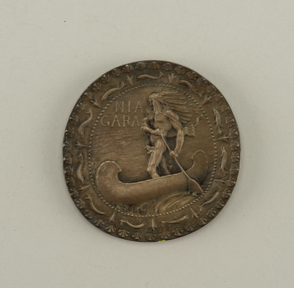 The medal shows a Native Chieftain standing in a canoe. Inscription in the field: Niagara. Border of dolphins alternating with arrowheads. Reverse: Not struck or cast, but simply engraved with the words: Niagara Medal. Frederick MacMonnies, Sculptor. Paulin Tasset, Engraver. The design of the Niagara medal is used in the seal of the Niagara power company, President Edward D. Adams.