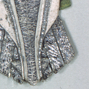 """Stomacher with a slightly u-shaped upper edge; the bottom finishes in a point with three independent tabs on either side. The front is linen, almost entirely covered with couched silver metallic yarns; while the metallic yarns are laid on horizontally, the couching stitches follow a """"V"""" pattern. In the center is a single rose tied with a bow. The rose was made separately from red and green silk and gold metallic yarn in a needle lace technique; it is sewn on top of the silver couching.  The center panel is trimmed with white silk piping and a narrow woven metal ribbon; eight green silk tabs project from the sides for pinning the stomacher in place. Stiffened with ribs of an unidentified material, and lined with block printed linen with a pattern of small birds in a scrolling vine in red on white."""