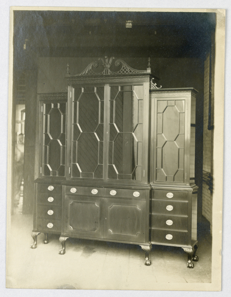 Tall china cabinet having slightly convex central segment consisting of 2 doors and 2 drawers, topped by large 2-door section surmounted by broken pediment consisting of scoll-like elements with fretwork and crown with 3 feathers center and finials either side; side cabinets consist of 4 drawers surmounted by large single-door section with carved Chinese fretwork; cabinet raised on 6 short cabriole legs with carved ball-and-claw feet.