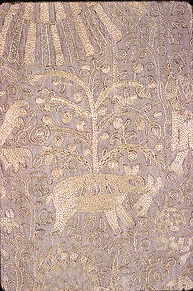 Embroidered cover, yellow silk on natural linen.  Double headed eagle in center plus same in four corners. The eagles are incorporated into a pattern which can be quartered containing a European horse and rider holding a sword, hunter on foot with gun, exotic beasts, domestic and wild animals, fish, crabs and trees.  At top and bottom on the center line is a vase with flowers. Border: symmetrical repeat of a bird and flowering plant with double headed eagle in a square in each corner. Guard stripe: symmetrical repeat of a curving vine hooked into an oval ring. Fringe attached all around.