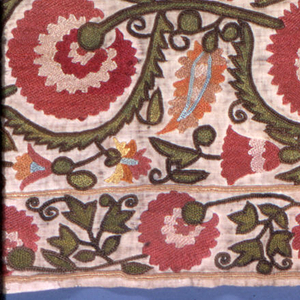 Hanging or cover embroidered in strong colors in silk on a natural cotton ground.  An eight-pointed star almost entirely fills the central square.  This is surrounded by a flowering vine.  Border also of flowering vine.