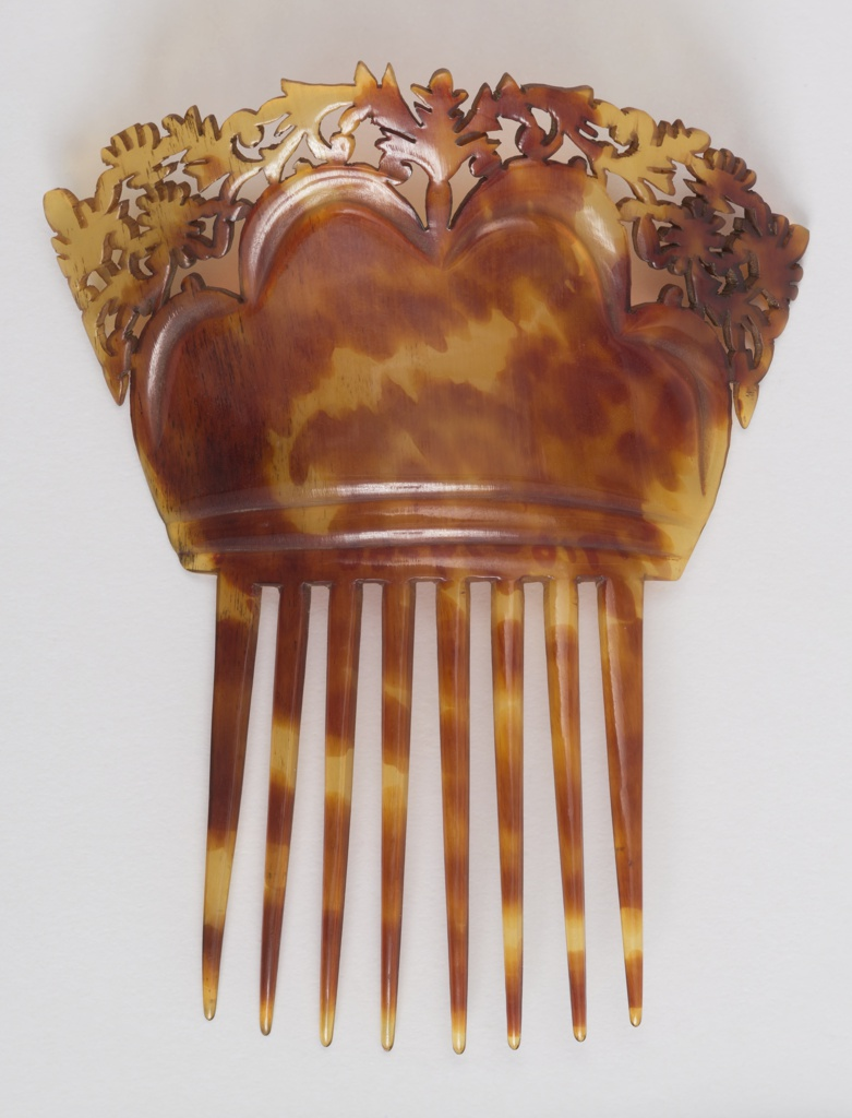Tortoiseshell comb with long teeth and stylized folate carving on top of carved scallops