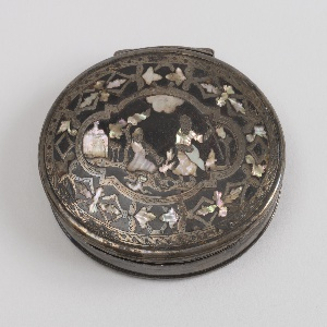 Oval shaped box with decorative lid  with an overlay of ornamentally cut  metal and an Eastern garden scene of mother of pearl