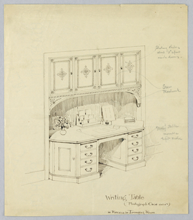 Writing desk in built-in niche; front has four small horizontal drawers on either side of open center; single vertical drawer set into both canted front corners; writing utensils, vase of flowers, and book on top; above, four vertical cupboard drawers supported by spandrels and with inlaid ornament.