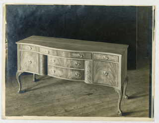 Oblong sideboard with 4 cabriole legs with animal paw feet, serpentine tri-partite front, and 2 drawers in recessed center section, flanked by 2 doors and topped by 3 conforming drawers.