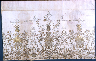 Panel for a skirt with three symmetrical floral motifs with curving leaves tied by a bow embroidered in gold.  Narrow border at bottom.