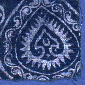 Repeating pattern in silver printed on a deep blue ground. Off-set tear-shaped framing devices with vine-and-leaf convention enclose stylized palmettes.  Much smaller inverted tear-shaped motifs containing rosettes in the interstices.