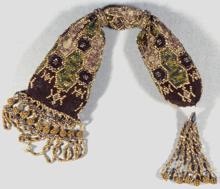 Miser's purse  in brown, cream, and soft pink silk netting in a honeycomb pattern, with gold-colored and cut-steel beads. The side opening is controlled by two cut steel rings. One end finished with tassel of twisted strands of beads, the other with a deep fringe of beads.