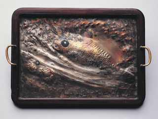 A rectangle textured copper tray with the impression of a fish and two small crabs framed in wood with handles on opposite sides.