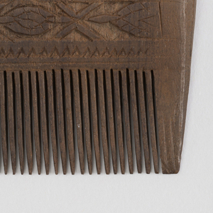 horizontal rectangle, with a band of oval paterae alternating with X's above a carved out background, all above the finely detailed comb teeth