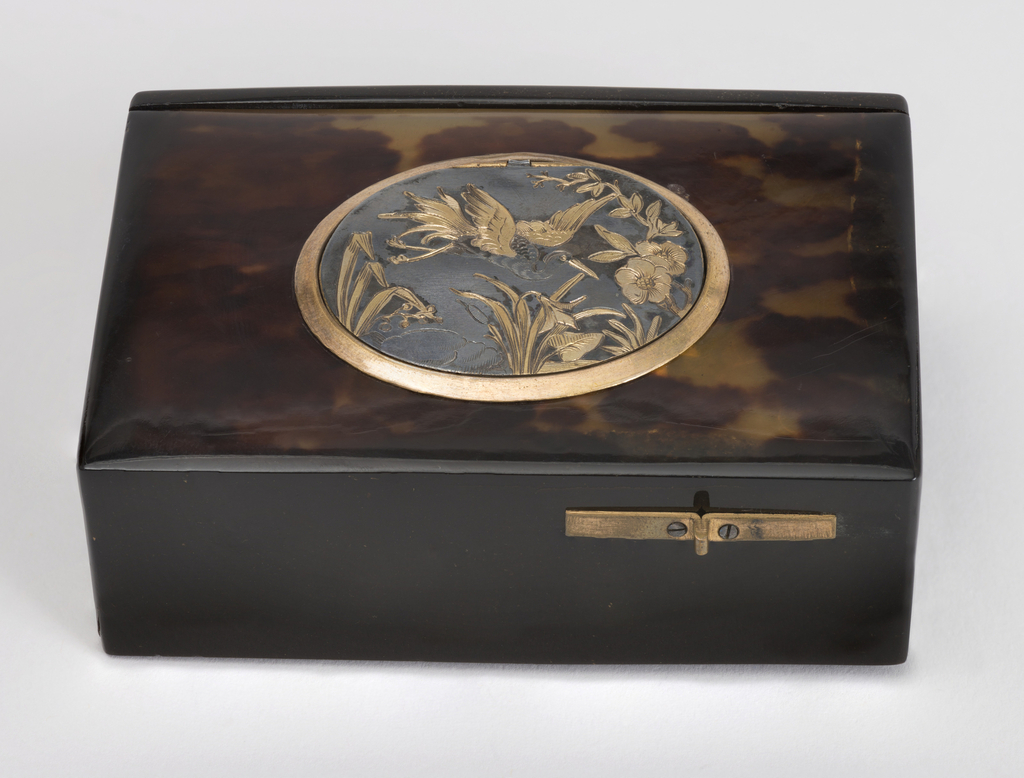 Rectangular tortoise shell box with hinged back, containing key. Oval, hinged and parcel-gilt medallion on top, engraved with flying crane and flowers. Catch on front of box opens this medallion and releases a small feather-covered bird. This automaton beats its wings, opens and closes its beak and pivots on a vertical axis while twittering. Beneath it, a cut-out medallion with and scrolls. B) a key