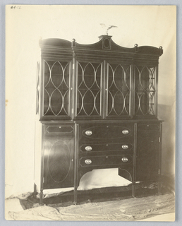 Tall china cabinet with tri-partite lower front consisting of 3 drawers flanked by 2 doors and molded top with sphere-shaped finials and carved eagle center.
